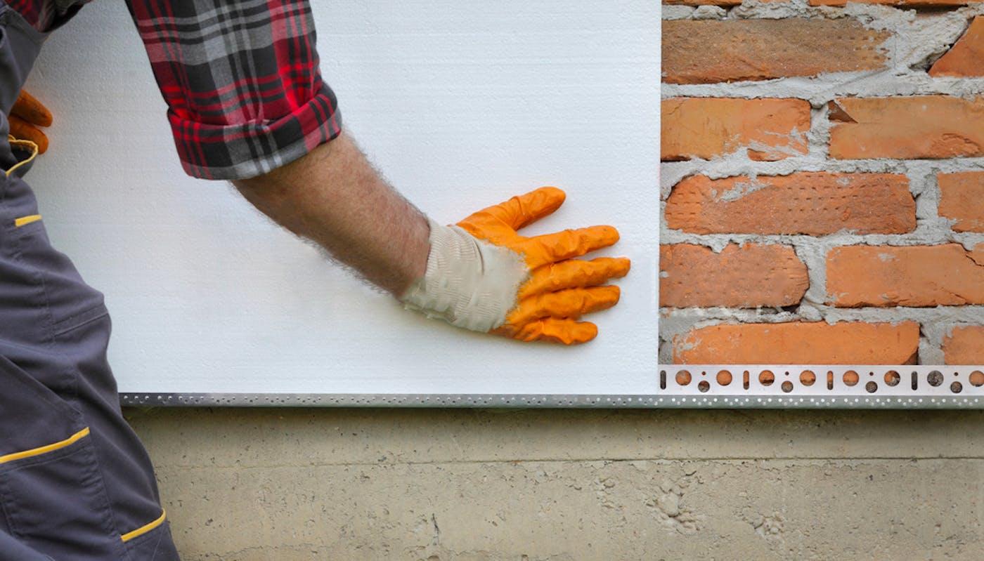 main d'un ouvrier posant l'isolation par l'extérieur