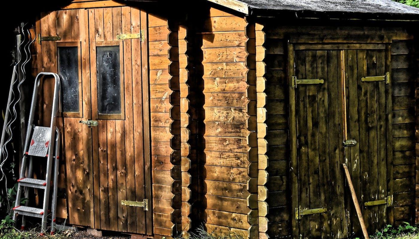 abri de jardin en bois avec escabeau posé sur la porte