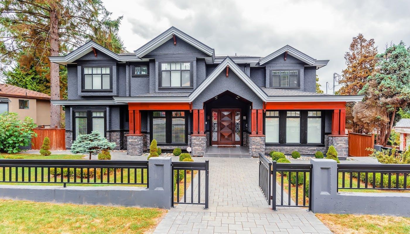 maison grise et rouge avec clôture en fer noir