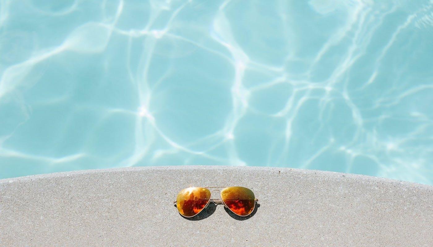 bord d'une piscine avec des lunettes de soleil posées