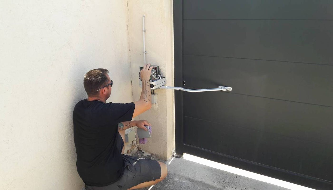 un ouvrier règle l'électricité d'un portail.