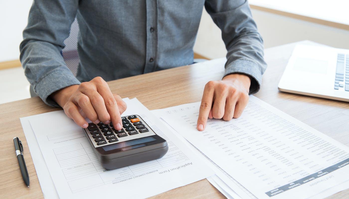 personne qui fait ses factures avec une calculette