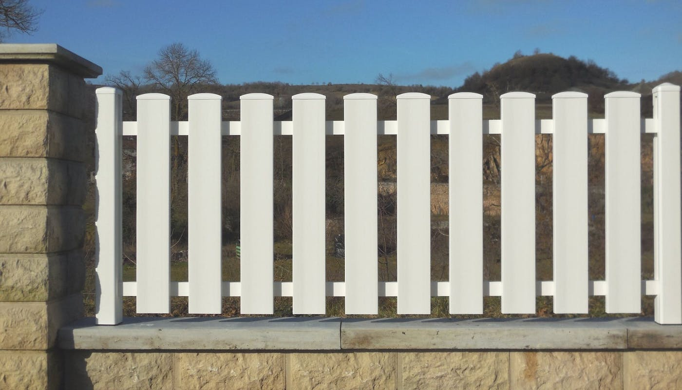clôture blanche en PVC sur un muret