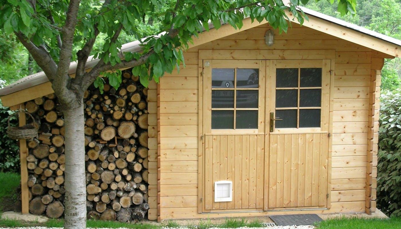 abri de jardin en bois avec un rangement pour bûches.