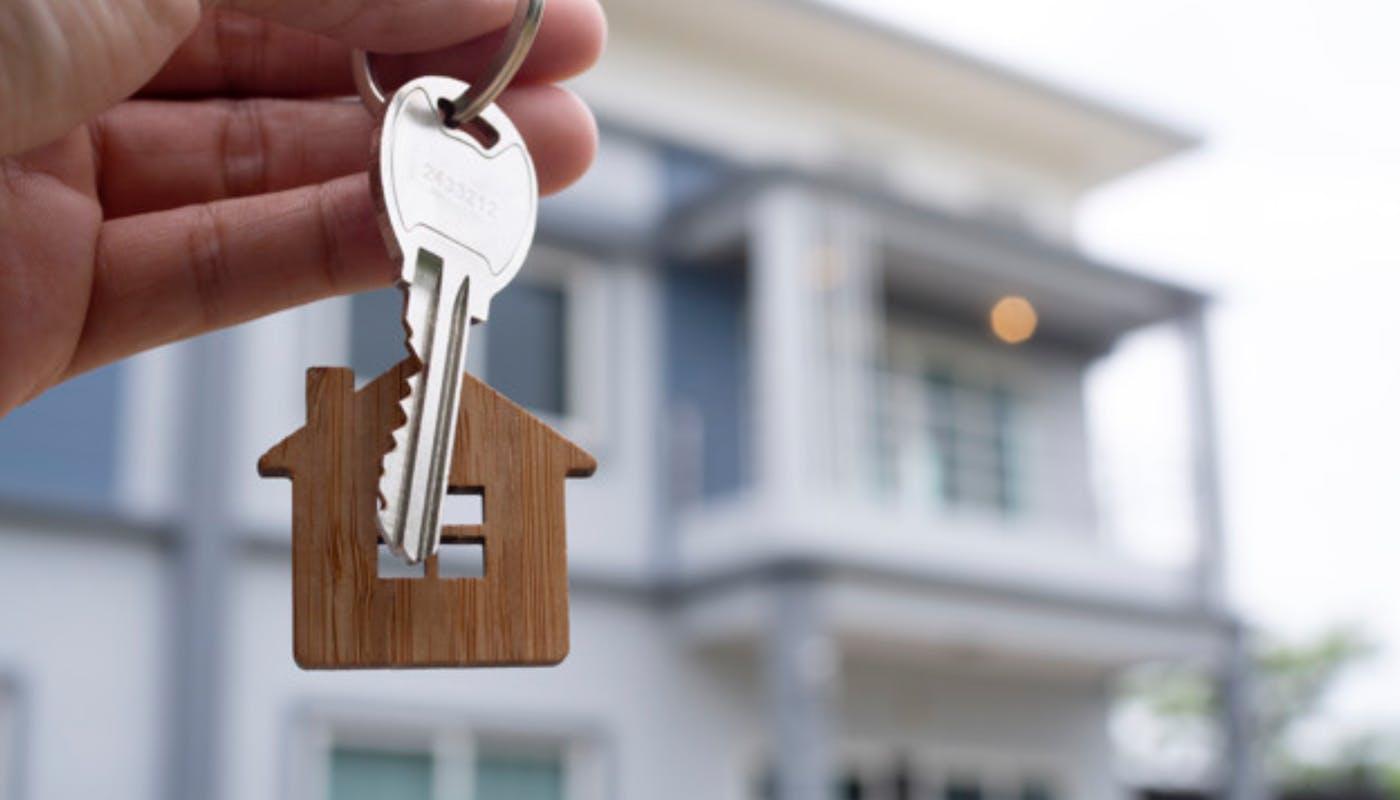 clé de maison avec un porte clé maison devant une maison