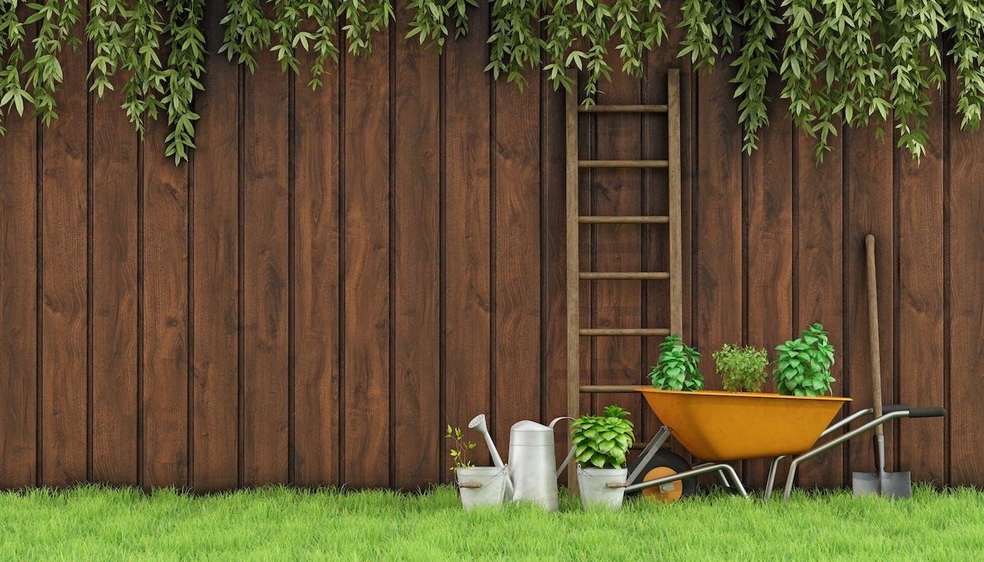 clôture en bois avec des outils de jardin