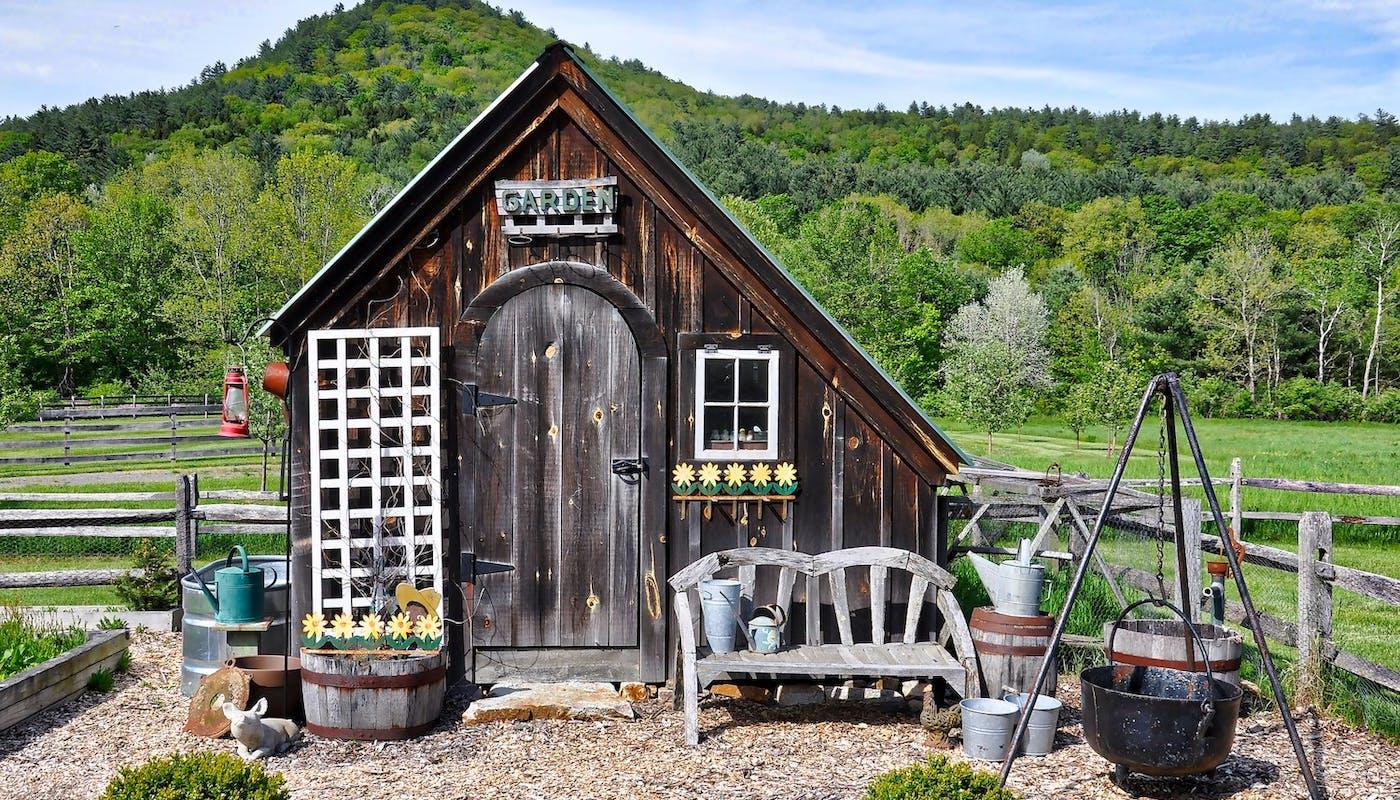 abri de jardin typique avec du matériel de jardinage devant