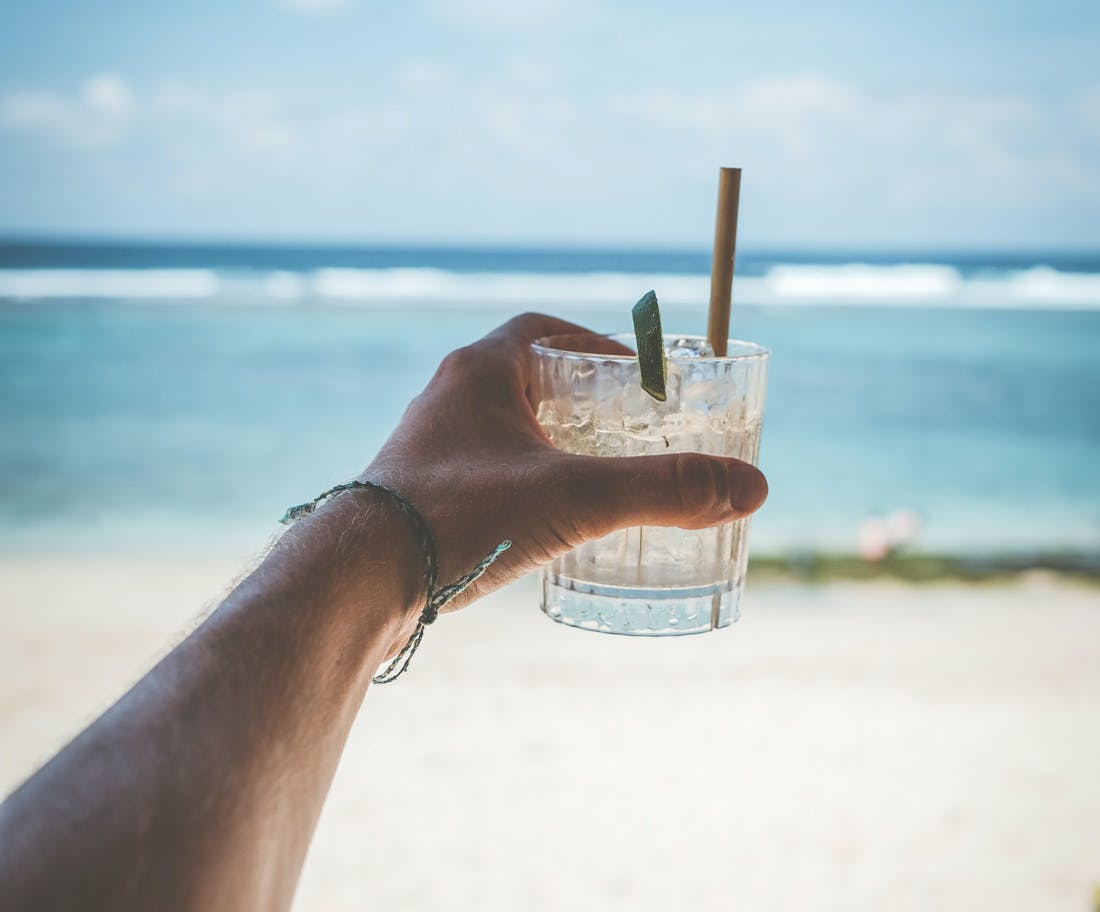 Image of a arm reaching out holding a cocktail looking out to the beach