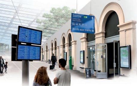Voyageurs en gare regardant des écrans d'information