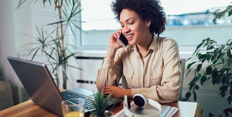 Home office: mulher trabalha no notebook enquanto fala no celular