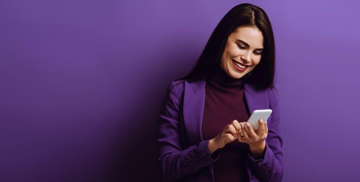 mulher sorri enquanto olha para o celular