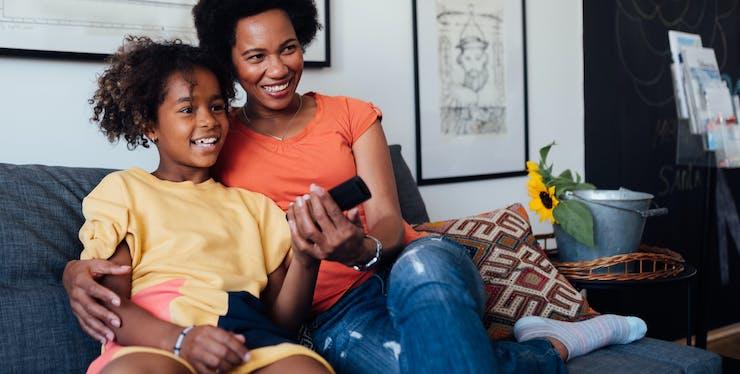 mãe e filho sentados no sofá, mexendo no controle remoto