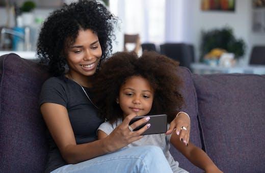 Celular com TV: mãe e filha assistem a programação
