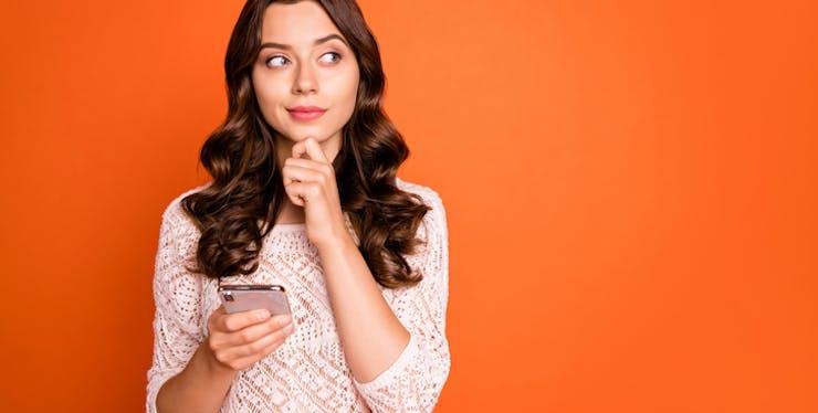 Mulher pensativa com o celular na mão