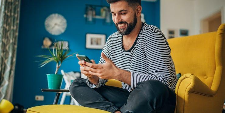 Homem sentado no sofá olhando o celular