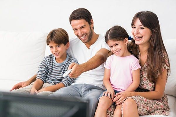 Vantagens SKY: família feliz assiste TV e pai aperta controle remoto