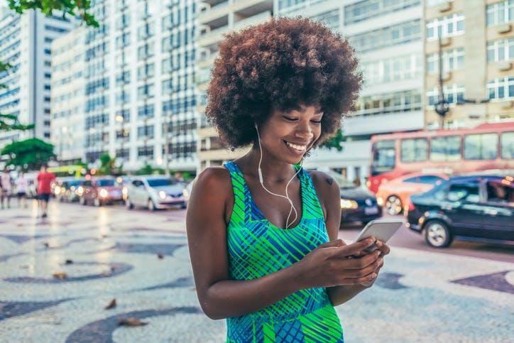 Mulher caminhando na rua e escutando música no celular com seu plano da Claro