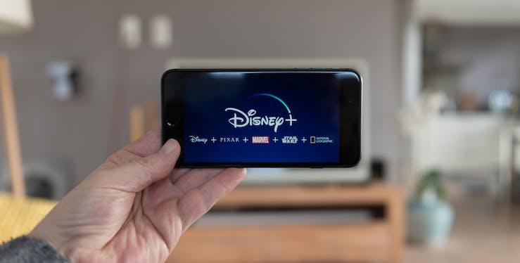 Pessoa segurando celular com tela principal do aplicativo Disney Plus