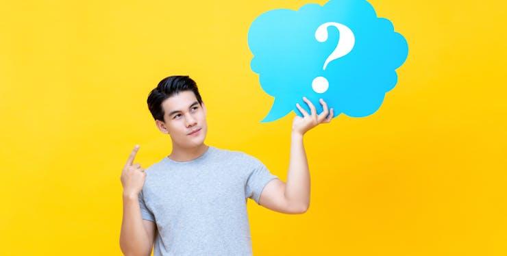 Homem segurando placa pensativa com ponto de interrogação