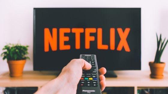 TIM Live Internet: televisão ligada na Netflix com mão aponto o controle para TV.