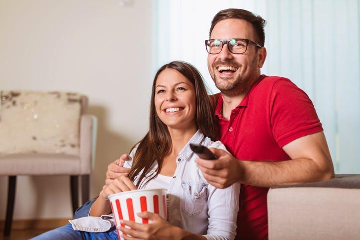 Recarga SKY: Homem e mulher assistem TV enquanto comem pipoca