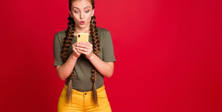Mulher olhando para o celular com expressão de surpresa