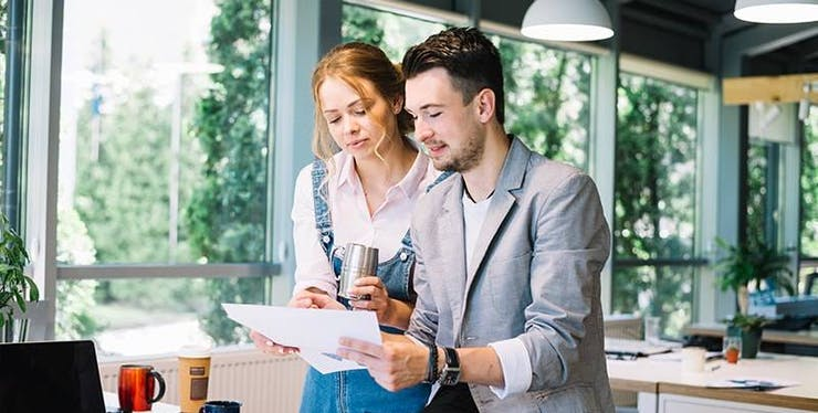 Homem e mulher olhando papéis