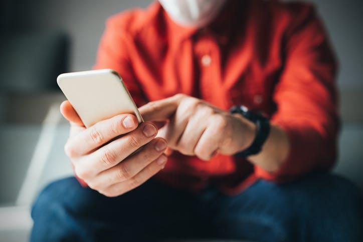 Homem sentado e mexendo no celular