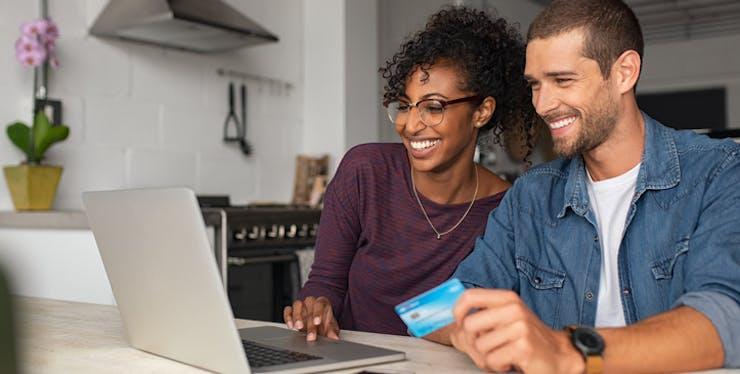 Compra segura pela internet: casal usando cartão de crédito e olhando notebook