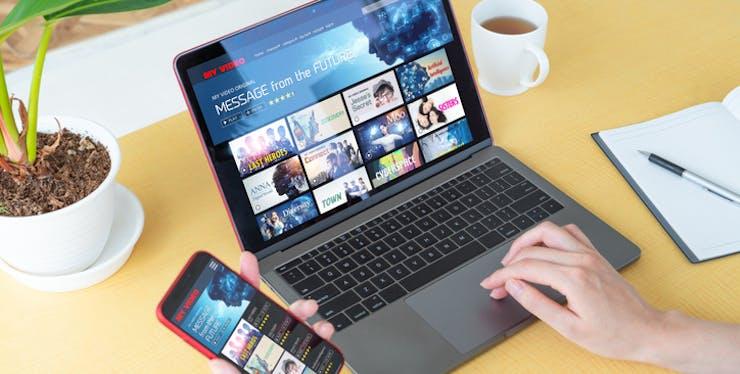 Pessoa usa aplicativo de filmes no celular e notebook