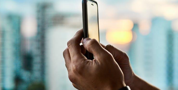 Mão de pessoa usando celular