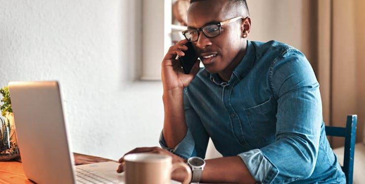 Homem falando ao telefone enquanto mexe no computador