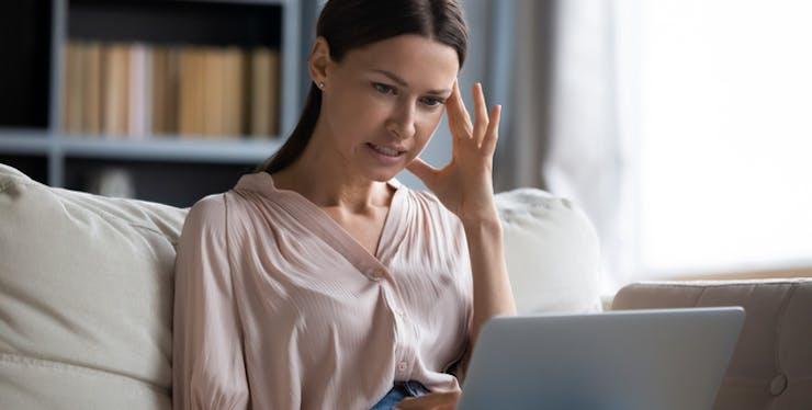 Mulher preocupada olhando para notebook