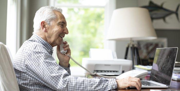 Homem idoso usando o telefone fixo