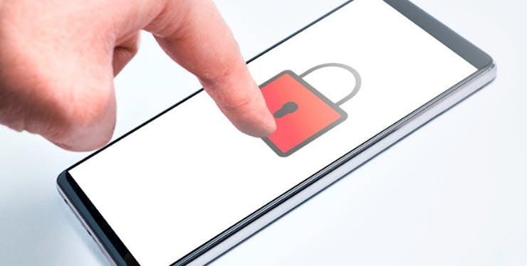 Bloqueio do WhatsApp: celular com imagem de cadeado e mão tentando desbloquear