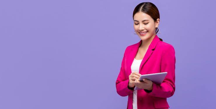 Mulher com roupa social e tablet em mãos.