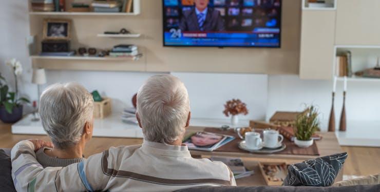 Casal idoso assiste TV digital na sala