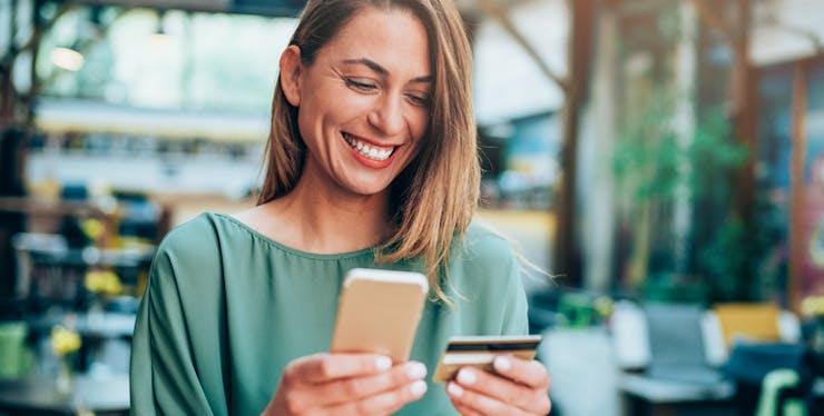 Mulher sorri enquanto usa celular e cartão de banco