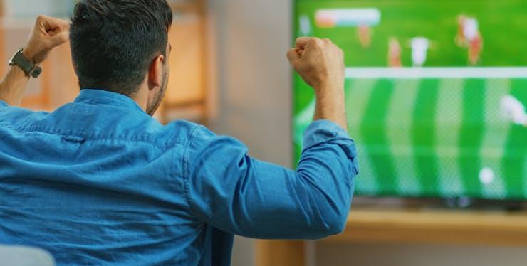 Homem vibra ao assistir a jogo de futebol na televisão