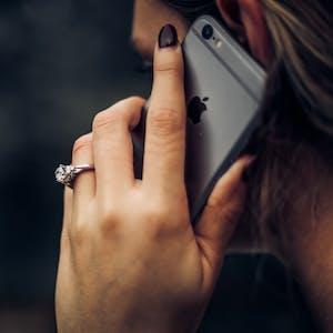 mulher fala ao telefone usando os benefícios tim
