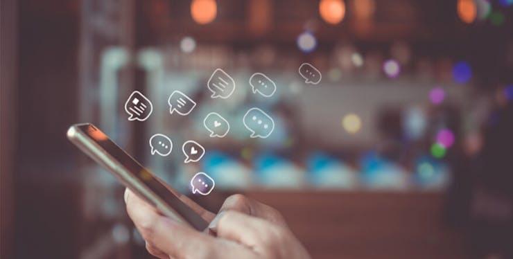 Redes sociais ilimitadas: celular com ilustrações de balões de fala e corações