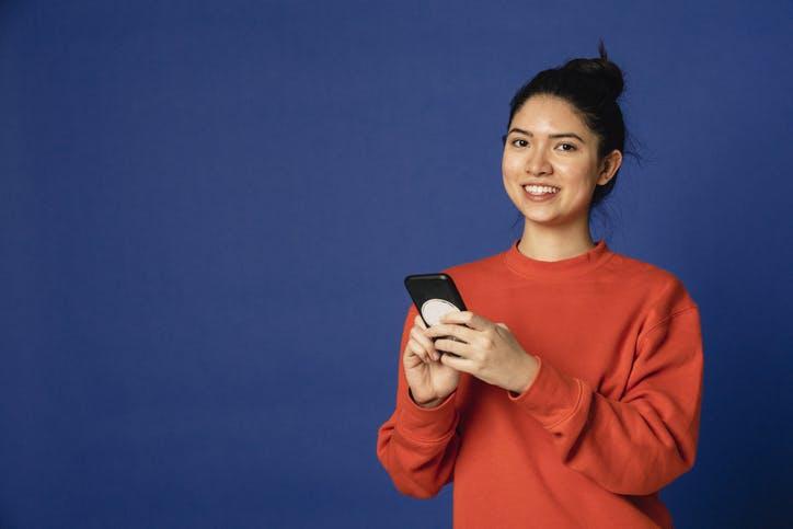 Mulher mexendo no celular com plano Claro celular