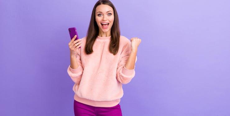 Moça feliz com o celular na mão