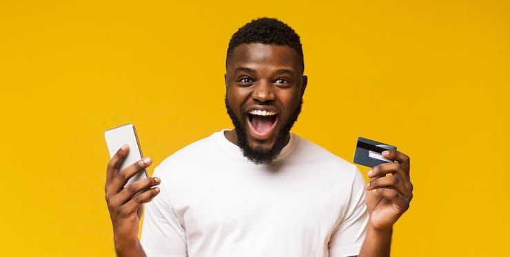 Homem segurando celular e cartão de crédito