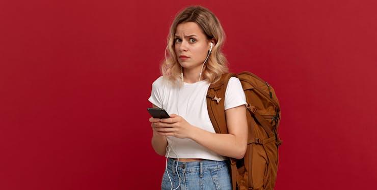 Moça com celular na mão e expressão de dúvida.