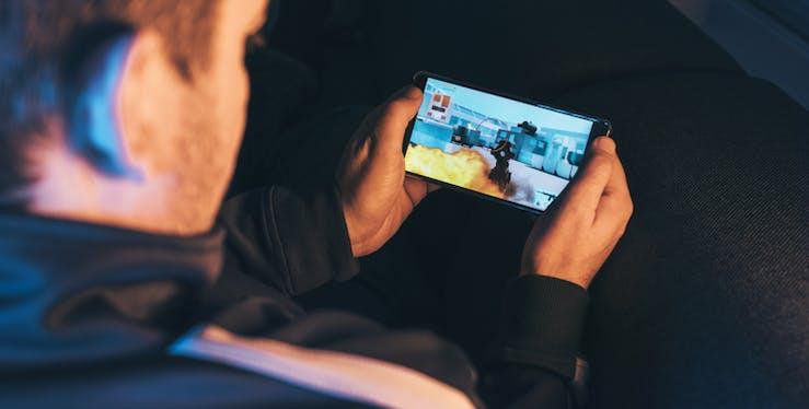 Homem jogando no celular.
