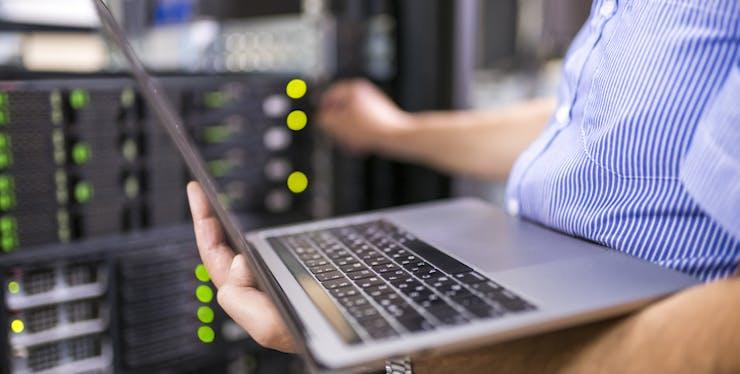 Pessoa com notebook nas mãos e conectando servidor para ter link dedicado