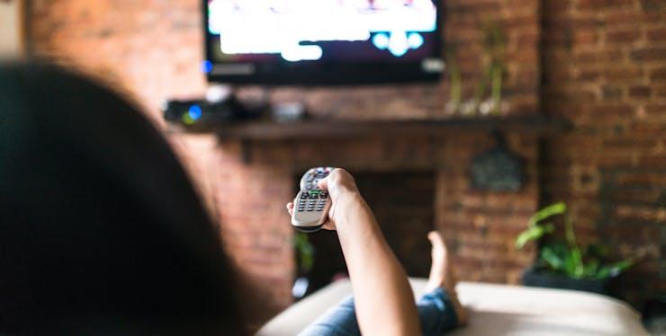 Mulher descansando assistindo TV