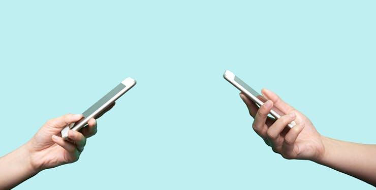 Mão segurando celular.