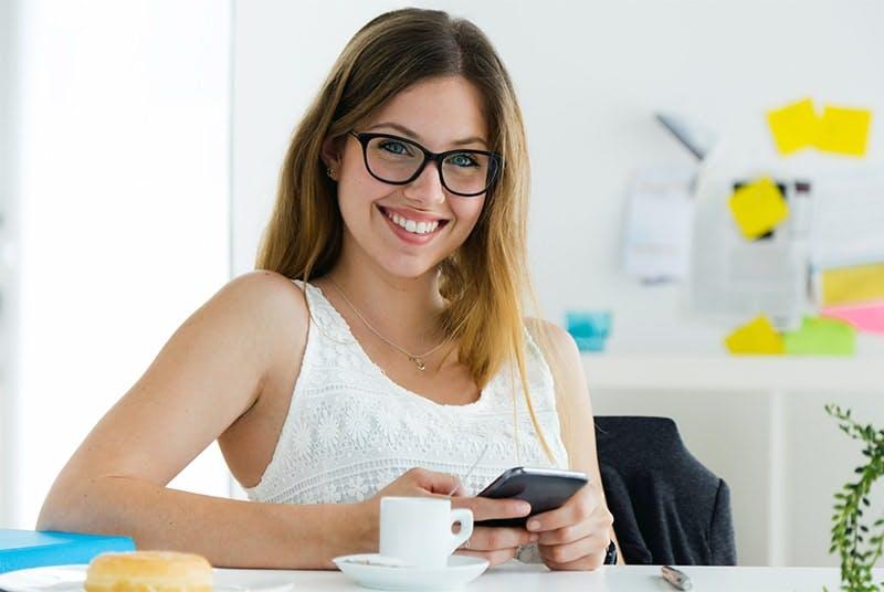 tim internet é boa? mulher sorrindo mexendo no celular